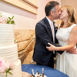 Bride and groom share a kiss after cutting their stunning three tiered white cake from Suarez bakery