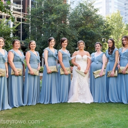 Bride poses with her bridesmaids wearing soft blue dresses and holding sparkling clutches before her summer wedding at The Mint