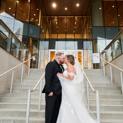Bride and groom share a kiss on the stairs of the Mint Museum Uptown during their summer wedding captured by Critsey Rowe Photography