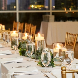 Candles and greenery were wonder accents to crisp white linens during a summer wedding in Uptown Charlotte coordinated by Magnificent Moments Weddings