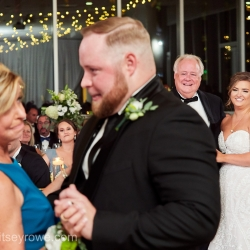Bride looks on as her groom dances with his mother during a summer wedding reception captured by Critsey Rowe Photography