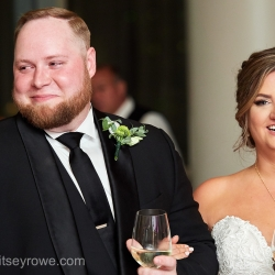 Bride and groom smile as their closest family and friends toast their new marriage during a reception coordinated by Magnificent Moments Weddings
