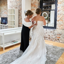 Brides mother helps button her dress and they put the finishing touches before getting married in an uptown ceremony coordinated by Magnificent Moments Weddings