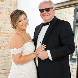 Bride poses with her father before her wedding ceremony at The Mint Museum Uptown