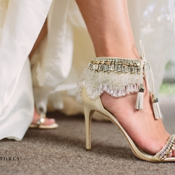 Bride shows of her stunning shoes complete with sparkler and tassels as she prepares to walk down the aisle at The Duke Mansion
