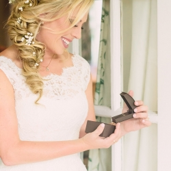 Bride opens sweet gift from her groom before her wedding coordinated by Magnificent Moments Weddings
