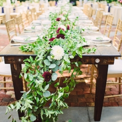 Overflowing greenery cascades down a farmhouse table for a garden wedding at The Duke Mansion in Charlotte North Carolina