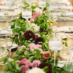 Stunning greenery garland fills a reception table at the Duke Mansion filled with blush and burgundy toned flowers and floating candles in glass vases all created by Lily Greenthumbs