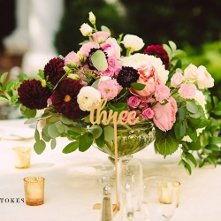 Glass compote vase serves as a stunning centerpiece filled with blush and burgundy toned flowers for a wedding at The Duke Mansion