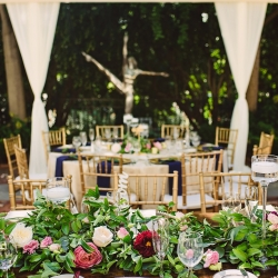 A garden wedding at the Duke Mansion featured lush greenery runners with blush toned flowers and glowing candle light created by Lily Greenthumbs