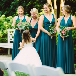 Bridesmaids wear stunning emerald green dresses while holding simple bouquets with a single blush flower created by Lily Greenthumbs
