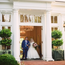 Bride enters down the aisle at the southern Duke Mansion between classic white columns and market lights