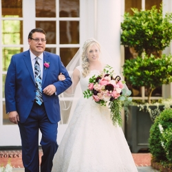 Bride escorted down the aisle to her groom carrying a stunning bridal bouquet full of blush and burgundy toned flowers by Lily Greenthumbs