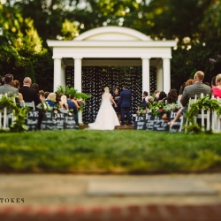 Garden ceremony at The Duke Mansion under a simple white pergola covered with cranes