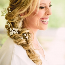 Bride has a stunning curled braid accented with baby's breath all done by Be Pretty