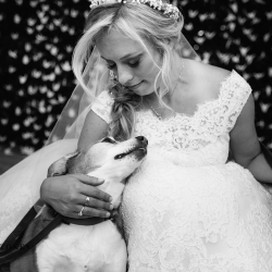 Bride poses with her dog in front of a custom crane backdrop before her garden wedding at The Duke Mansion