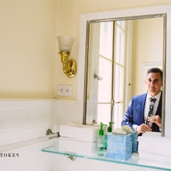 Groom prepares for his wedding by straightening his floral tie all captured by Crystal Stokes Photography