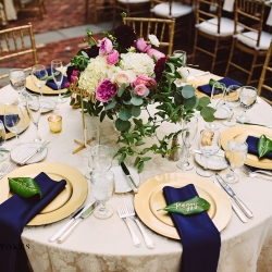 Elegant table setting features gold chargers, navy napkins, and custom leaf place settings for a wedding at The Duke Mansion coordinated by Magnificent Moments Weddings