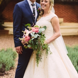 Bride and groom pose in the gardens of the Duke Mansion with a stunning bridal bouquet featuring pink roses and lush greenery accents created by Lily Greenthumbs