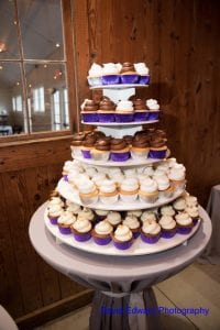 Cupcake tower overflowing with vanilla and chocolate cakes created by Brenda's Cake Gallery for a spring wedding at The Diary Barn