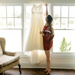 Bride hangs her dress as she prepares for her wedding at Morning Glory Farm in Monroe, North Carolina