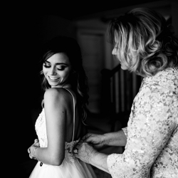 Brides mother helps her get into her dress before her fall wedding at Morning Glory Farms