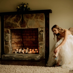 Bride puts on her shoes in front of the fireplace at Morning Glory Farms