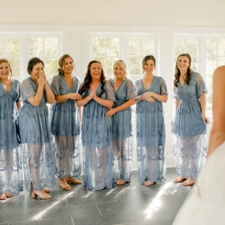 Bridesmaids react to seeing the bride in her stunning dress with lace bodice and full skirt
