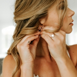 Bride putting on earrings as she prepares for her fall wedding coordinated by Magnificent Moments Weddings