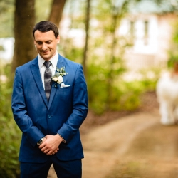 Groom eagerly awaits his bride during their first look at Morning Glory Farms