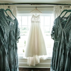 A brides stunning lace dress is surrounded by her bridesmaids elegant lace bridesmaids dress at Morning Glory Farm before a fall wedding