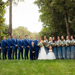 Bride and Groom pose with their entire bridal party among the tall trees of Morning Glory Farms for their fall wedding coordinated by Magnificent Moments Weddings