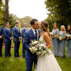 Bride and groom share a kiss while surrounded by their bridal party at Morning Glory Farms