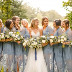 Bride poses with her bridesmaids dressed in soft blue dresses with lace overlays for a fall wedding coordinated by Magnificent Moments Weddings