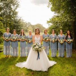 Bride poses with her bridesmaids all holding stunning white bouquets with accents of soft blue created by Narcisse Greenway Designs