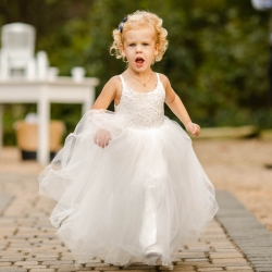 A little flower girl full of energy makes her way down the aisle during a fall wedding at Morning Glory Farms