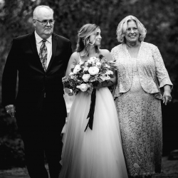 A bride is escorted down the aisle by her mother and father during an intimate wedding ceremony coordinated by Magnificent Moments Weddings