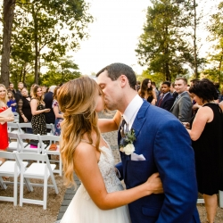 Bride and groom share a kiss after exiting their outdoor ceremony at Morning Glory Farms coordinated by Magnificent Moments Weddings