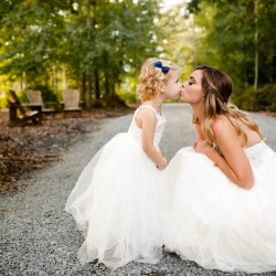 Bride shares a kiss with her little flower girl who is dressed in white with a sweet navy bow in her hair