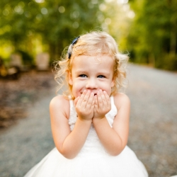 Flower girl shows off her smile to David Mendoza III Photography during at wedding at Morning Glory Farms