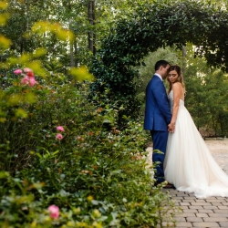 Bride and groom embrace under a stunning greenery arch on the property of Morning Glory Farms