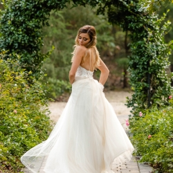 A bride shows of her stunning dress with lace bodice while standing under a greenery arch at Morning Glory Farms
