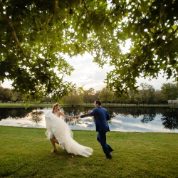 Bride and groom share a fun moment in front for a small pond on the property of Morning Glory Farms during their fall wedding