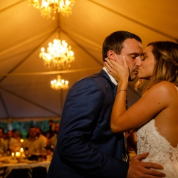 Bride and groom share a kiss during their Morning Glory Farms wedding reception coordinated by Magnificent Moments Weddings