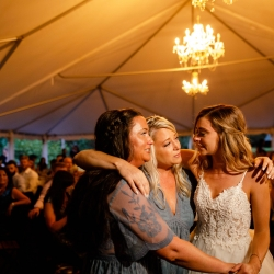 Bride shares a sweet moment with her bridesmaids on the dance floor during a stunning tent accented with delicate chandeliers
