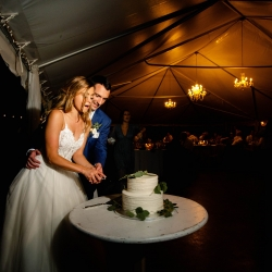 A bride and groom cut their simple two tier white cake from Publix during their wedding reception at Morning Glory Farms captured by David Mendoza III Photography