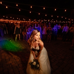 Bride prepares to toss her bouquet during a wedding reception coordinated by Magnificent Moments Weddings