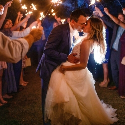 Bride and groom share a kiss surrounded by a sea of sparklers in a grande exit coordinated by Magnificent Moments Weddings for a fall wedding at Morning Glory Farms