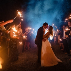 Bride and groom share a kiss during their sparkler exit at Morning Glory Farms captured by David Mendoza III Photography