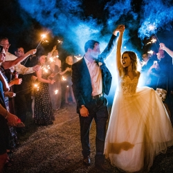 Bride and groom leave their wedding through a sparkler grande exit coordinated by Magnificent Moments Weddings